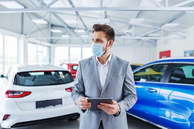 Venditore di auto con maschera facciale in piedi nel salone dell'auto e utilizzo di tablet per il controllo della birra chiara online.