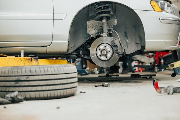 Concetto di centro di assistenza auto, veicolo sollevato in ascensore alla stazione di manutenzione, riparazione e controllo di autoveicoli, riparazione dell'auto
