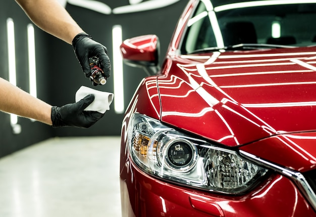 Addetto al servizio auto che applica il rivestimento nano su un dettaglio dell'auto.