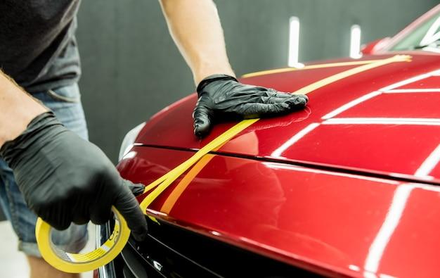 Addetto al servizio auto che applica nastro protettivo sui dettagli dell'auto prima della lucidatura.