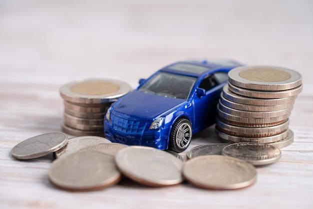 Auto sulla pila di monete. prestito auto, finanza, risparmio di denaro, assicurazioni e concetti di tempo di leasing.
