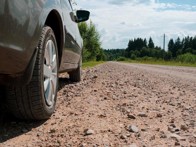 L'auto si trova su una strada di campagna polverosa, ruota da vicino
