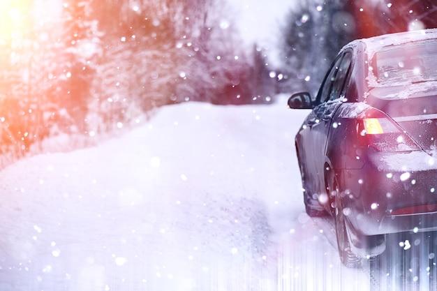 L'auto si trova su una strada coperta di neve in una giornata nuvolosa invernale