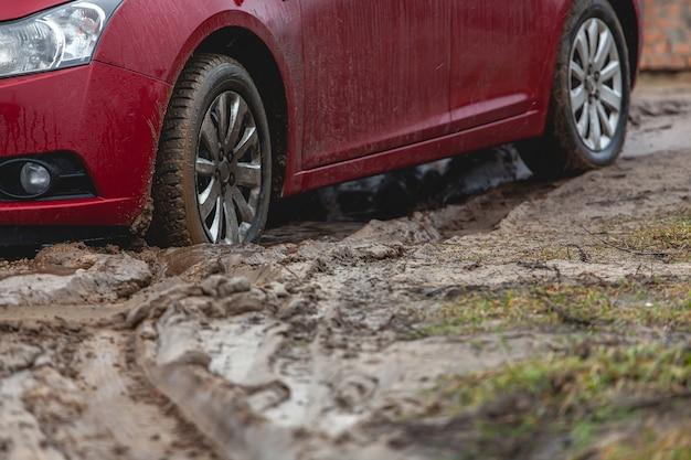 Macchina bloccata nel fango, ruota della macchina in una pozzanghera sporca, terreno accidentato