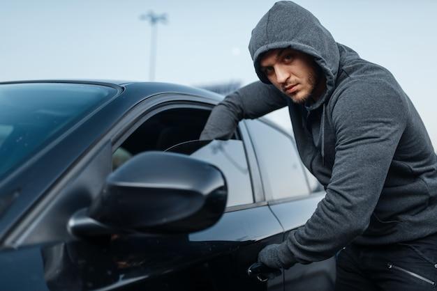 Ladro di auto che rompe la porta, lavoro criminale, ladro, furto.