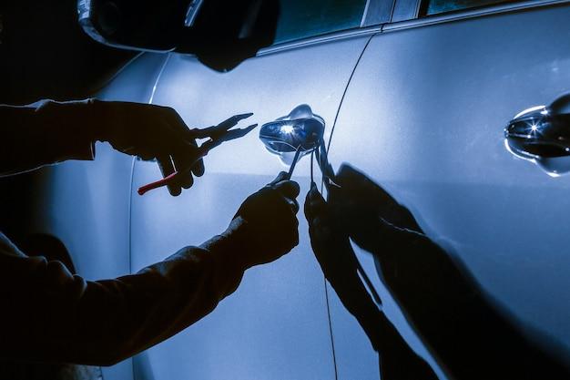 Ladro d'auto che usa uno strumento per irrompere in un'auto