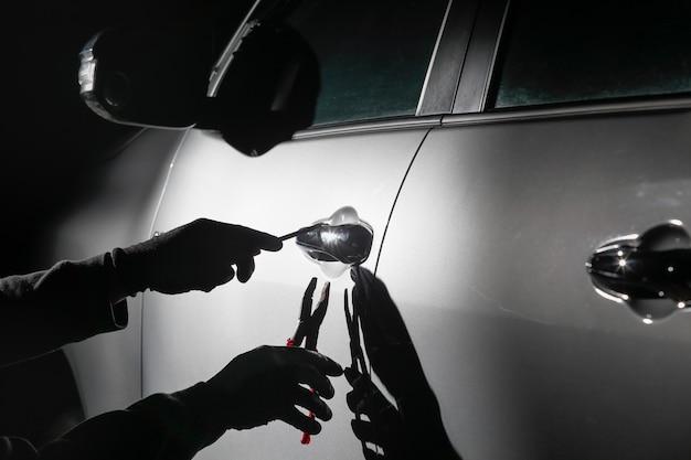 Ladro d'auto usando uno strumento per irrompere in un'auto