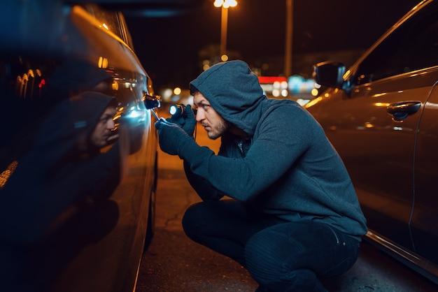 Ladro di auto con un cacciavite che rompe la serratura della porta. veicolo di apertura del ladro maschio incappucciato sul parcheggio. rapina automobilistica, crimine automobilistico