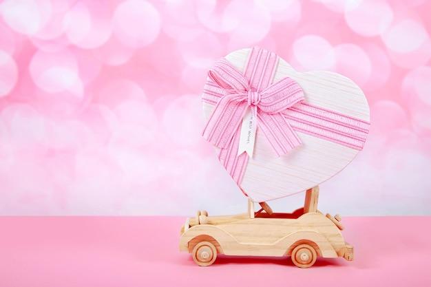 Giocattolo auto con un regalo e un fiocco a forma di cuore su uno sfondo rosa con bokeh