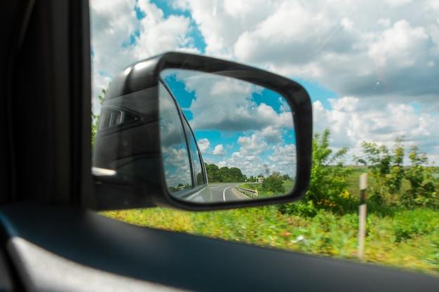 Riflessione della strada di concetto di viaggio dell'automobile nello spazio della copia di vista dello specchietto retrovisore