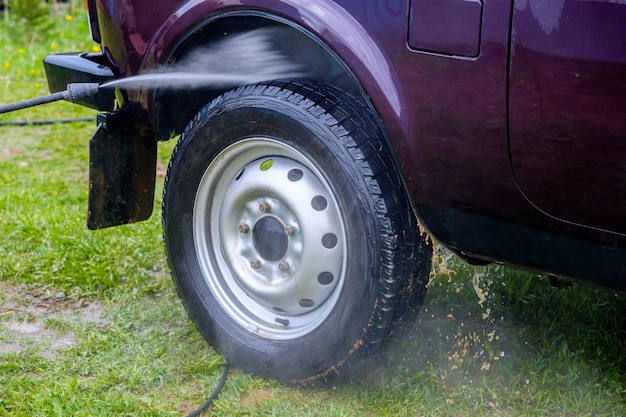 Lavaggio auto pomeridiano all'aperto con apparecchio ad alta pressione. un potente getto d'acqua schizza via lo sporco dalla carrozzeria viola dell'auto, da vetri, ruote e pneumatici.