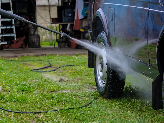 Lavaggio auto pomeridiano all'aperto con apparecchio ad alta pressione
