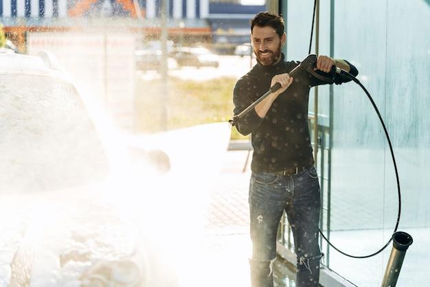 Autolavaggio. uomo caucasico felice che lava l'auto nel posto speciale. autolavaggio con concetto di pistola ad alta pressione. foto d'archivio