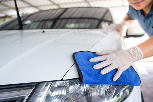 Il personale del servizio di autolavaggio pulisce le auto con panni in microfibra. dettagli e concetto di cameriere messa a fuoco selettiva vista ravvicinata