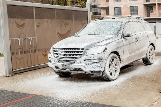 Autolavaggio con schiuma nella stazione di autolavaggio. autolavaggio. lavatrice alla stazione. concetto di lavaggio auto. auto in schiuma.