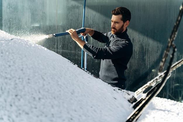 Autolavaggio con pistola ad alta pressione. uomo caucasico concentrato che lava l'auto nel posto speciale. concetto di autolavaggio. foto d'archivio