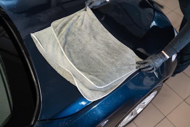 L'operaio dell'autolavaggio pulisce l'auto dopo il lavaggio con un asciugamano in microfibra.