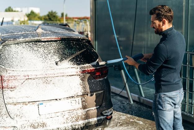 Lavaggio auto dal suo proprietario caucasico. vista posteriore dell'uomo che pulisce la sua automobile con acqua ad alta pressione in strada durante l'estate