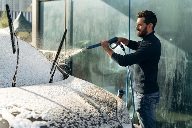 Lavaggio auto. autolavaggio nel posto speciale da solo. uomo che sorride alla telecamera mentre lava l'auto nera. pulizia dell'auto utilizzando il concetto di acqua ad alta pressione
