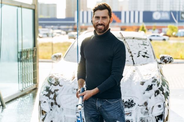 Lavaggio auto. pulizia auto con acqua ad alta pressione. autolavaggio nel posto speciale da solo. uomo che sorride alla telecamera mentre lava l'auto nera