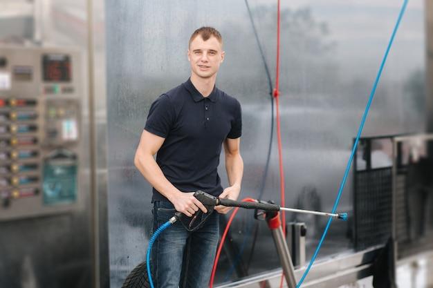 Lavaggio auto. auto di pulizia utilizzando cera ad alta pressione per shinig. uomo che lava la sua auto all'aperto.
