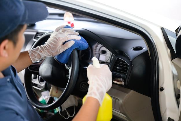 Servizio di lavaggio e pulizia auto utilizzare un panno per pulire l'interno dell'auto con spray detergente per interni.