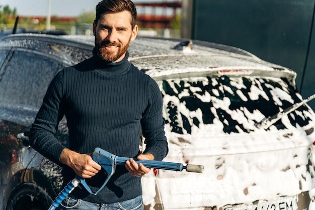 Lavaggio auto. mezzo busto verticale dell'uomo caucasico che tiene in mano un'attrezzatura speciale e sorride alla telecamera. pulizia auto utilizzando il concetto di acqua ad alta pressione. messa a fuoco selettiva