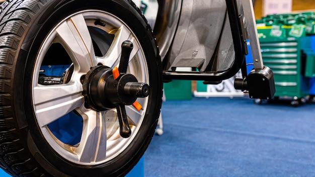Una ruota di automobile su una macchina di bilanciamento della ruota di automobile automatizzata nel garage.