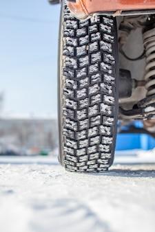 Ruota di automobile sulla neve in primo piano invernale. le sospensioni e il telaio dell'auto sono visibili. l'auto è parcheggiata in un parcheggio innevato.