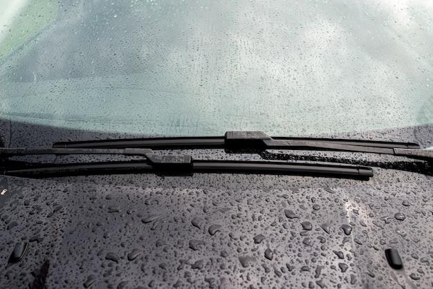 Parabrezza dell'auto con gocce di pioggia e primo piano del tergicristallo senza telaio.