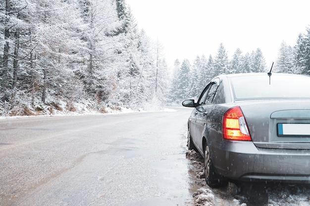 Auto su una strada invernale nella foresta