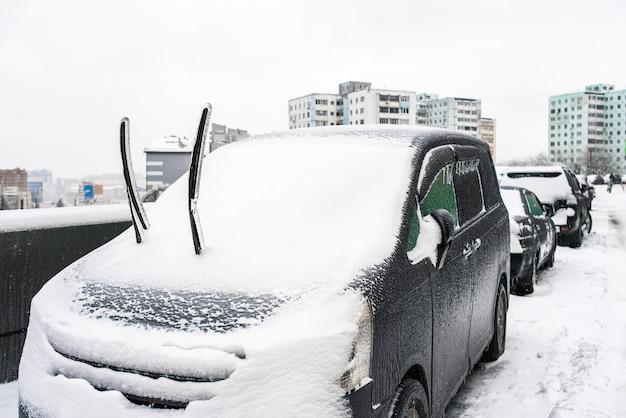 Tergicristalli auto coperti di ghiaccio e neve dopo la pioggia gelata da vicino ciclone tempesta di ghiaccio tempo nevoso scene gelide invernali