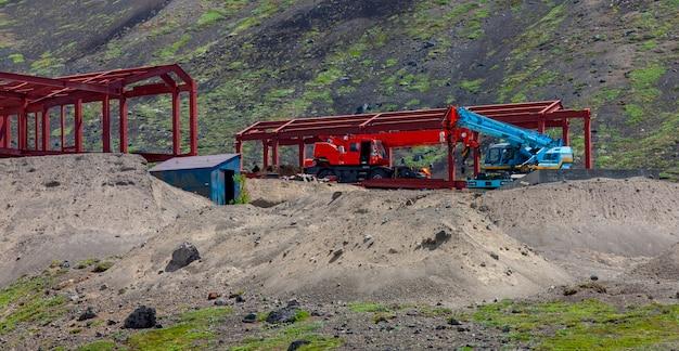 L'auto con una gru sulla costruzione della montagna