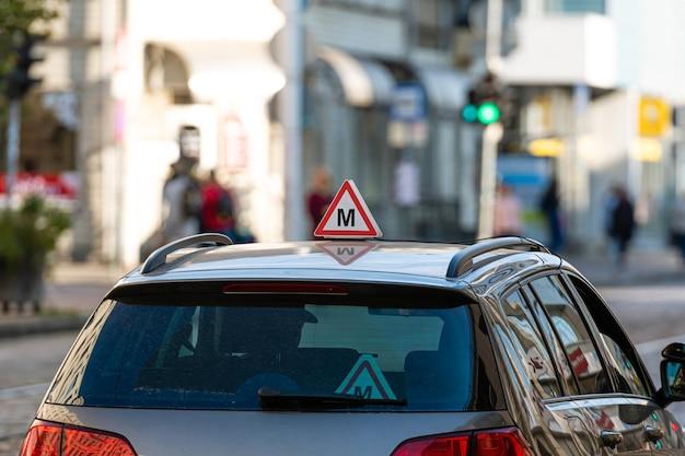 Auto con segno di scuola guida lettone sul tetto, strada sfocati con semafori