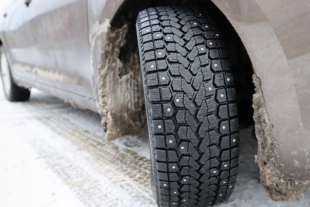 Un'auto con pneumatici invernali e spuntoni su una strada innevata con nevischio