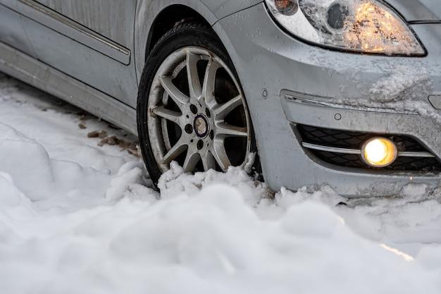 Auto con pneumatici invernali in strada innevata all'aperto, pneumatici in inverno sulla neve, primo piano