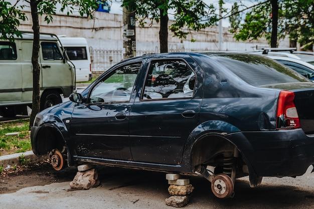 Un'auto senza ruote è per strada i ladri hanno usato pietre per parcheggiare l'auto atti vandalici