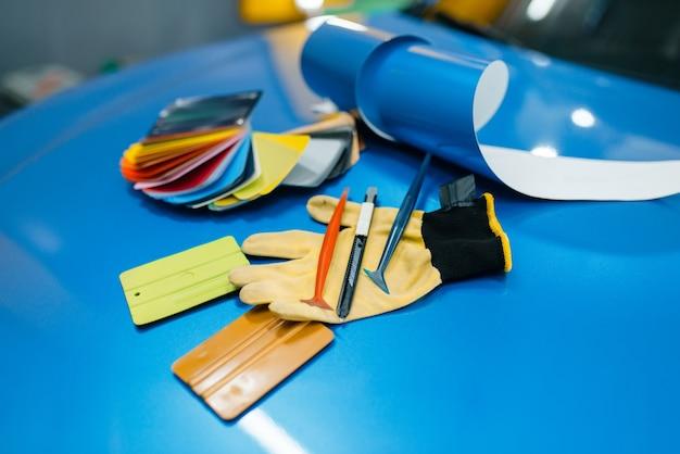 Car wrapping, pellicola protettiva in vinile o tavolozza dei colori della pellicola e strumenti di installazione sul primo piano del veicolo. dettagli automatici