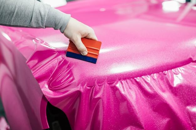 Specialista di car wrapping che mette pellicola o pellicola in vinile sull'auto. messa a fuoco selettiva.