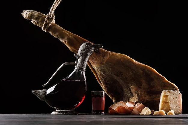 Una caraffa di vino a forma di anatra, un bicchiere di vino, una coscia di prosciutto di parma e formaggio. sfondo nero.