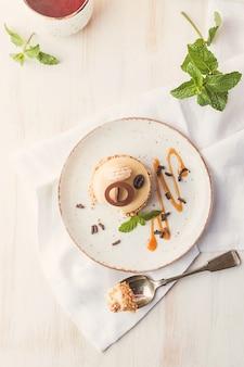 Torta di caffè al caramello in una glassa con i dadi sulla piastra su sfondo bianco vista dall'alto
