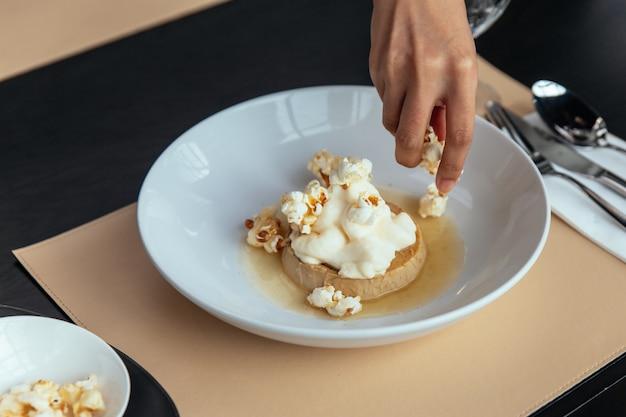 Crema pasticcera al caramello con crema che si topping a mano con popcorn.