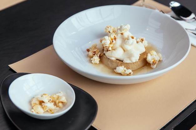 Crema pasticcera al caramello con crema che si abbina al popcorn. servito nel piatto bianco.