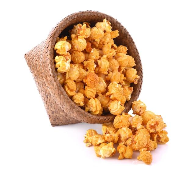 Popcorn al caramello in cestino su sfondo bianco