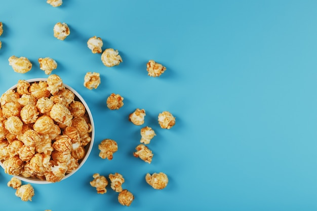 Popcorn al caramello in una tazza su uno sfondo blu, vista dall'alto.