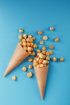 Popcorn al caramello in una busta di carta su uno sfondo blu.