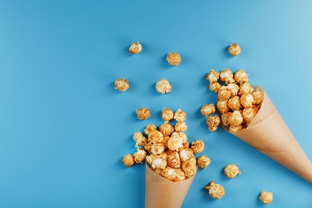Popcorn al caramello in una busta di carta su un blu.