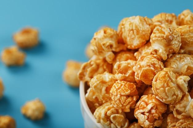 Popcorn al caramello in una tazza di vetro bianco con le forbici su sfondo blu