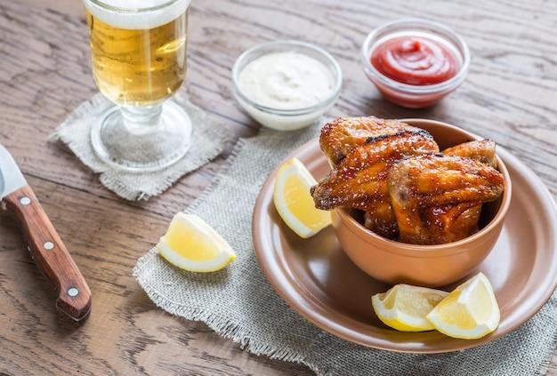 Ali di pollo caramellate con un bicchiere di birra