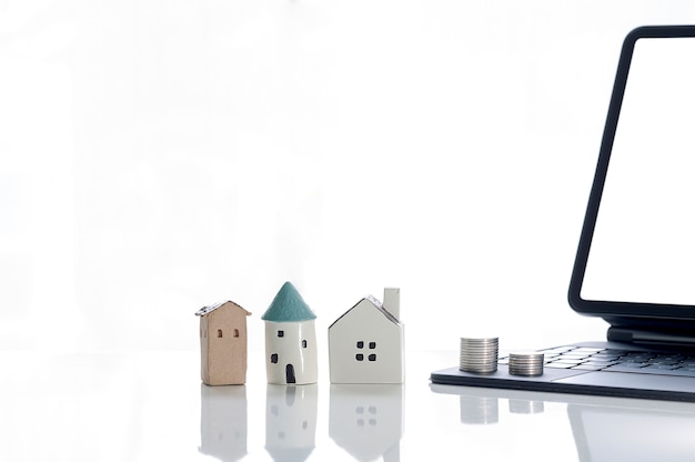 Modello di casa caramic, pila di monete e tablet sul tavolo bianco.